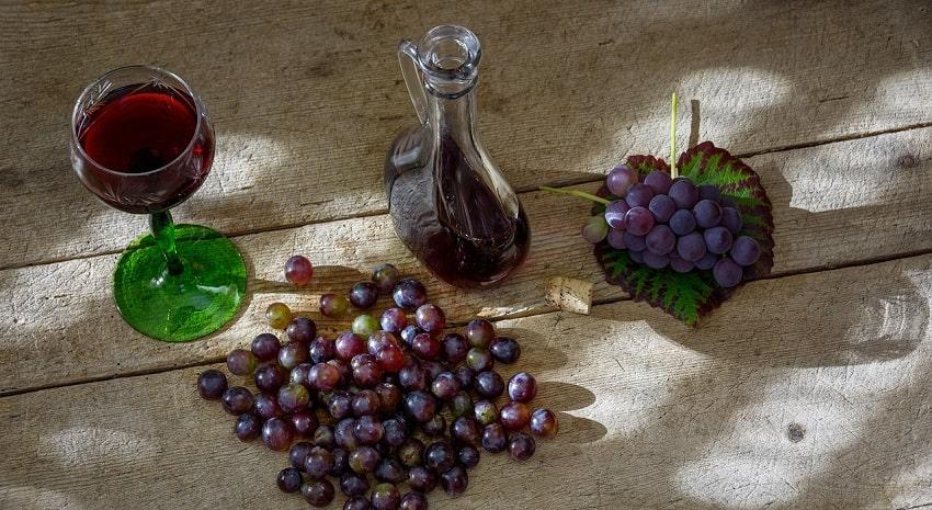 Tavola con un bicchiere e una bottiglia di vino rosso e uva